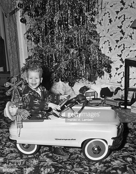 A young boy wearing a robe smiles while sitting at the wheel of a toy 'torpedo' car with a Howdy Doody doll next to him in front of a Christmas tree...