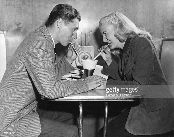 A young couple hold hands and smile while sharing an ice cream soda with two straws at a booth in a diner