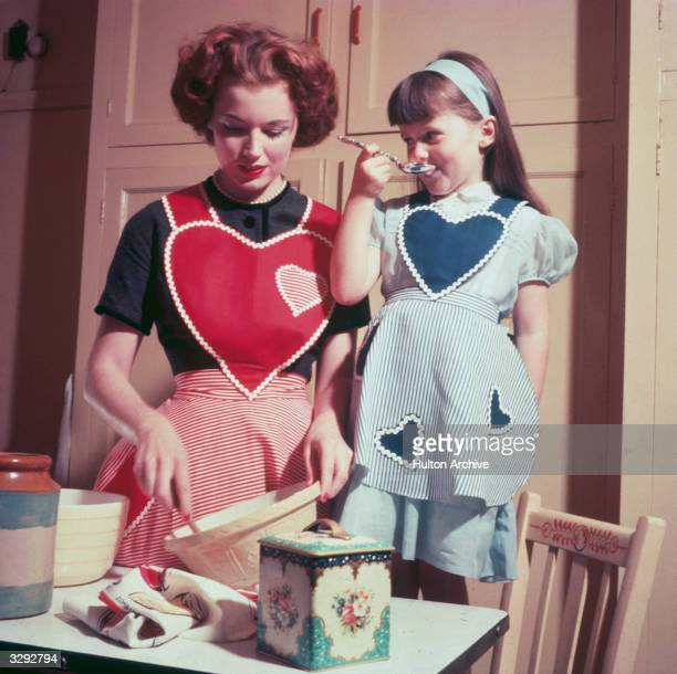 A young girl helps in the kitchen while her mother bakes a cake