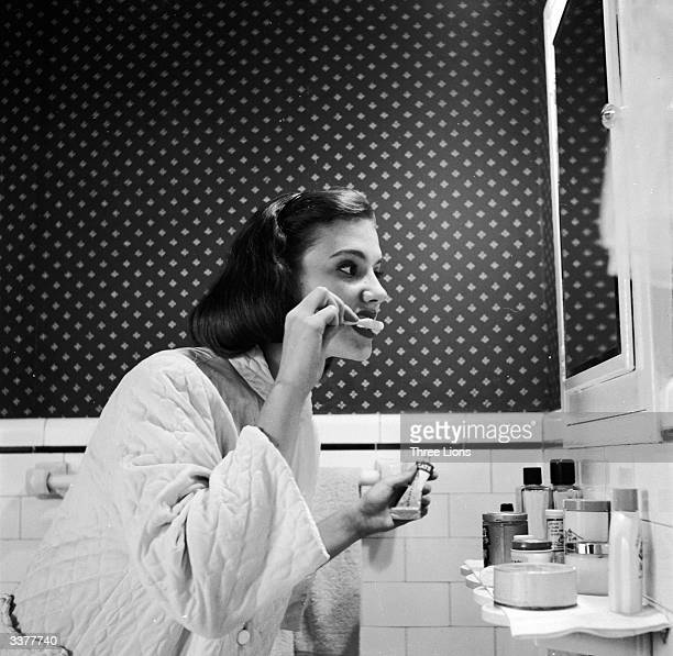 A young woman brushing her teeth in her bathroom