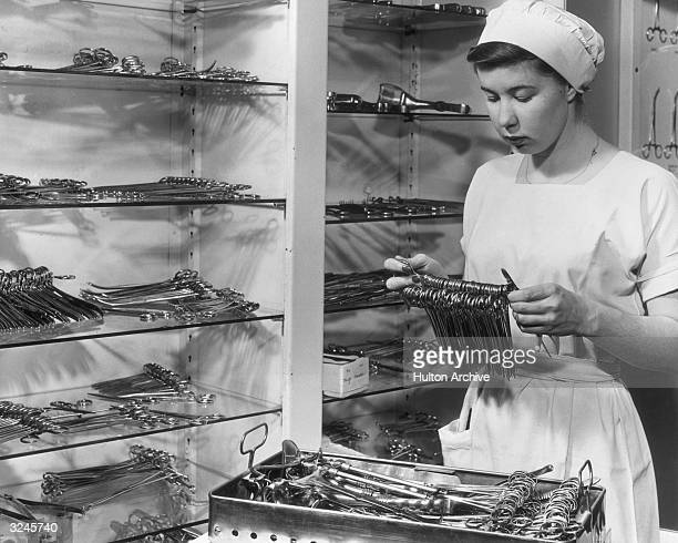 A young woman in a uniform holds a supply of sterilized metal forceps in front of a cabinet of dental instruments