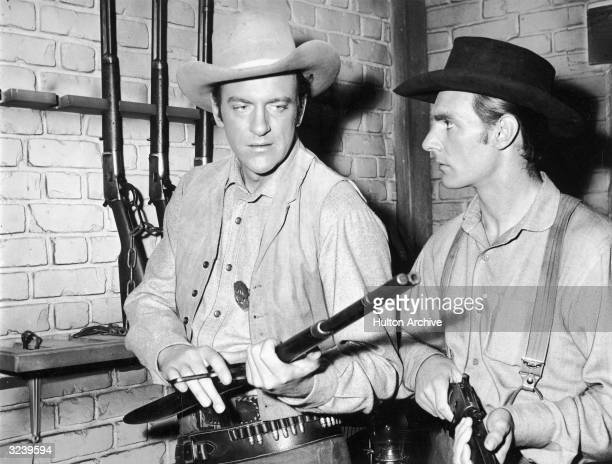 Actors James Arness as Marshall Matt Dillon and Dennis Weaver inspect rifles from a rack in a still from the television series 'Gunsmoke'