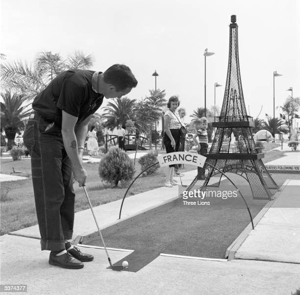 Aiming the ball under a model of the Eiffel Tower on the miniature golf course at Pontchartrain beach Louisiana