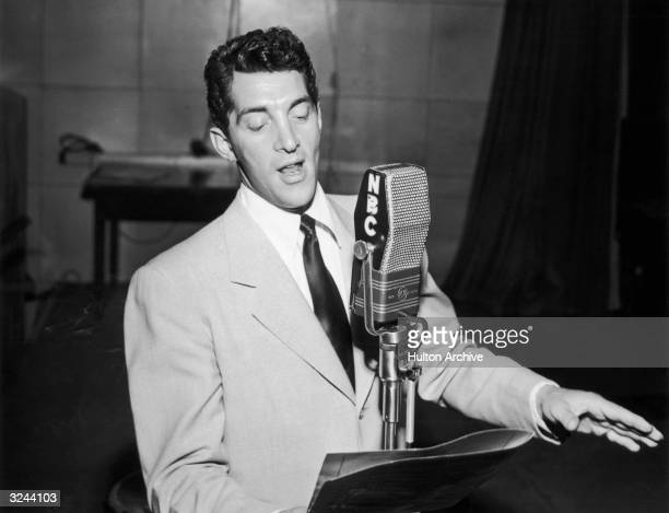 American actor and singer Dean Martin stands behind a microphone looking at a music stand and singing with one hand out inside the NBC radio studios