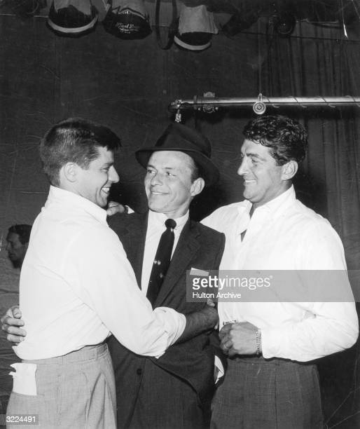 American actor and singer Frank Sinatra is hugged by American actor and comedian Jerry Lewis and actor and singer Dean Martin on the set of a Martin...