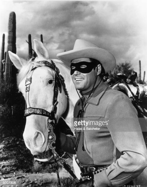 American actor Clayton Moore dressed in costume as 'The Lone Ranger' stands next to his horse in a desert setting in a promotional portrait for the...