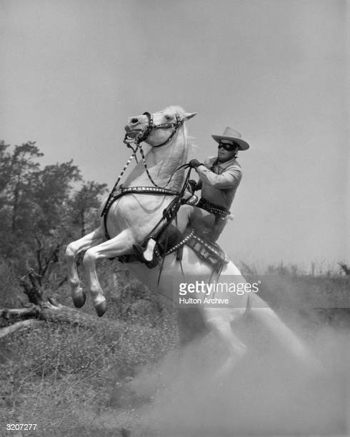 American actor Clayton Moore in masked costume as 'The Lone Ranger' rears back on his horse Silver in a still from the American television series...