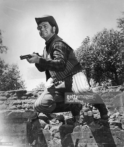 American actor Ernest Borgnine kneels on a stone wall while aiming his rifle in a still from an unidentified Western film He wears a cowboy hat and...