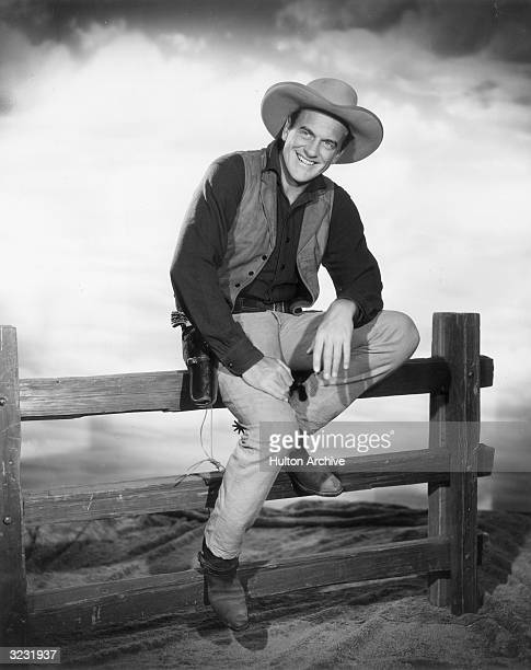 American actor James Arness wears a Western costume while sitting on a fence in a promotional portrait for the television series 'Gunsmoke' 1950s...