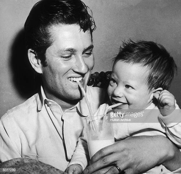 American actor John Drew Barrymore holds his eightmonthold infant son John Blyth Barrymore while each uses a straw to drink milk from the same glass