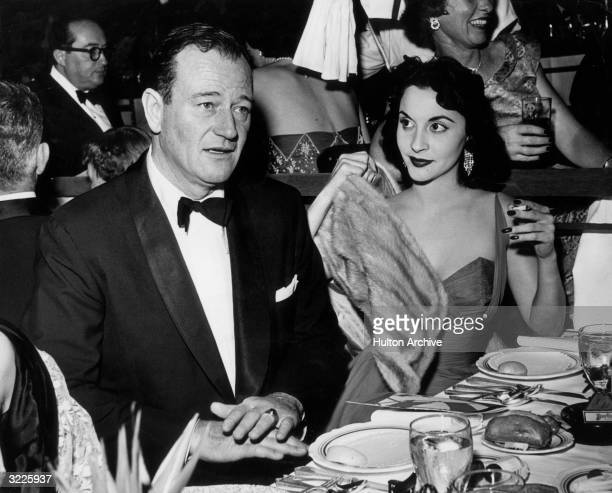 American actor John Wayne seated at a table with his wife Pilar Palette during a dinner party Wayne is wearing a tuxedo and is speaking Palette is...