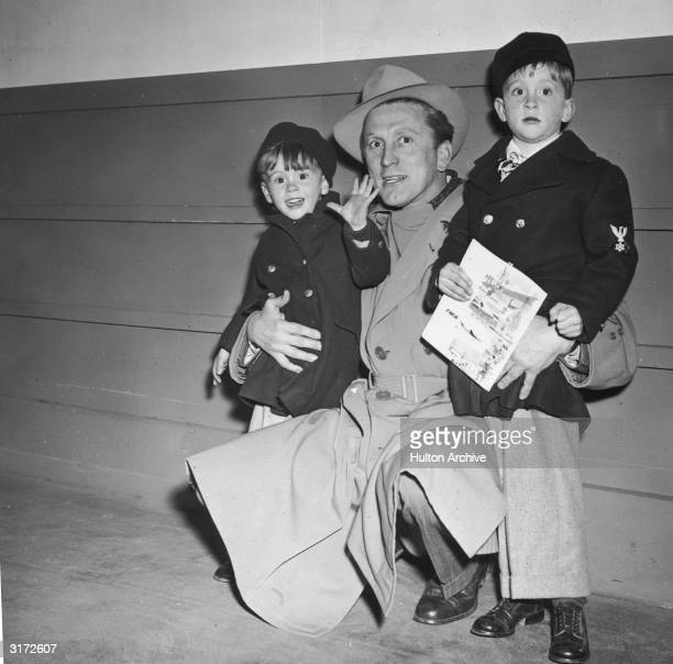 American actor Kirk Douglas kneels beside his sons Joel and Michael All three wear winter coats Michael is carrying a comic book
