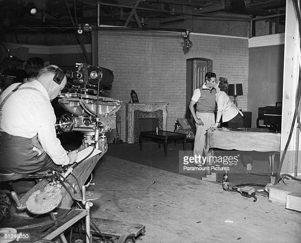 Circa 1955, American actor Lucille Ball and her husband, Cuban-born bandleader and actor Desi Arnaz , kiss on the set of their television series, 'I...