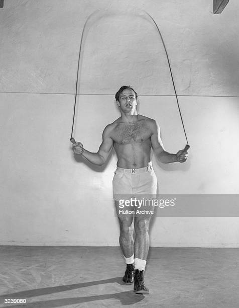 American actor Marlon Brando jumps rope wearing boots shorts and no shirt