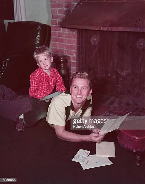 American actor Michael Douglas as a young boy, lounging with his father, the American actor Kirk Douglas, in front of a brick fireplace. Kirk is...