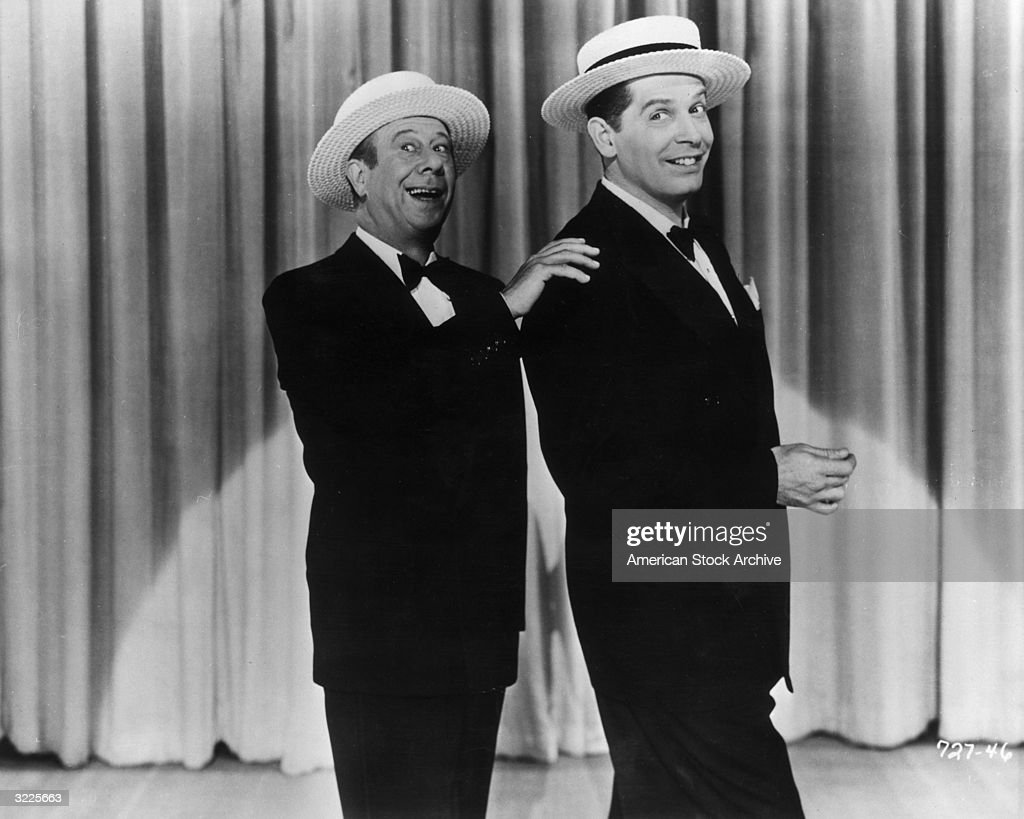 American actors and comedians Bert Lahr (L) and Milton Berle (1908 - 2002) smile while performing on stage together in tuxedos and straw hats.