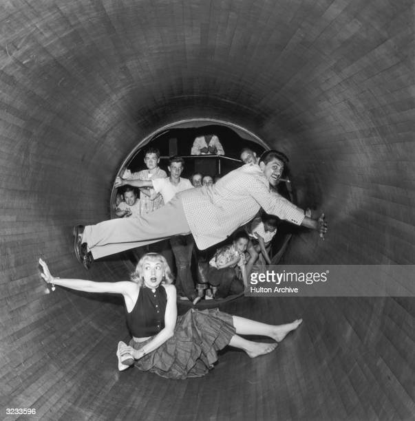 American actors Ernie Kovacs smoking a cigar and Edie Adams pose inside a cylindrical spinning amusement park ride while children watch from the...