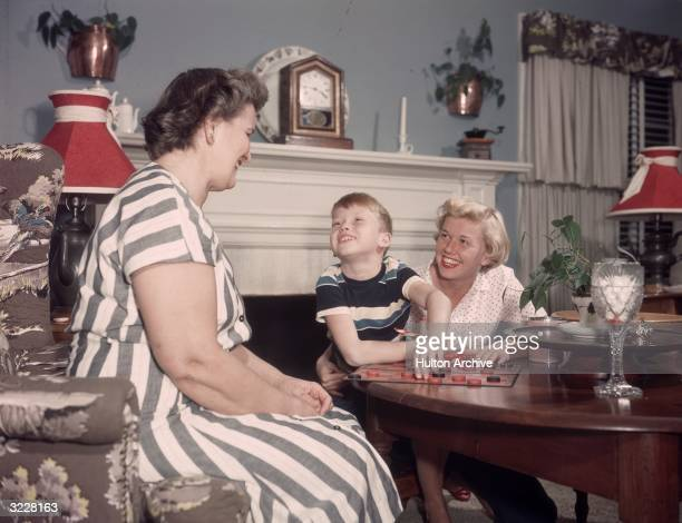 American actress Doris Day and her son, Terry Melcher, playing checkers with another woman, possibly Day's mother, in a living room. Day's son is...