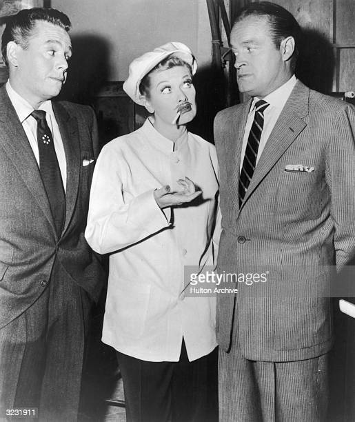 American actress Lucille Ball , wearing a mustache and cap with a cigarette hanging from her mouth, receives a strange look from British-born...
