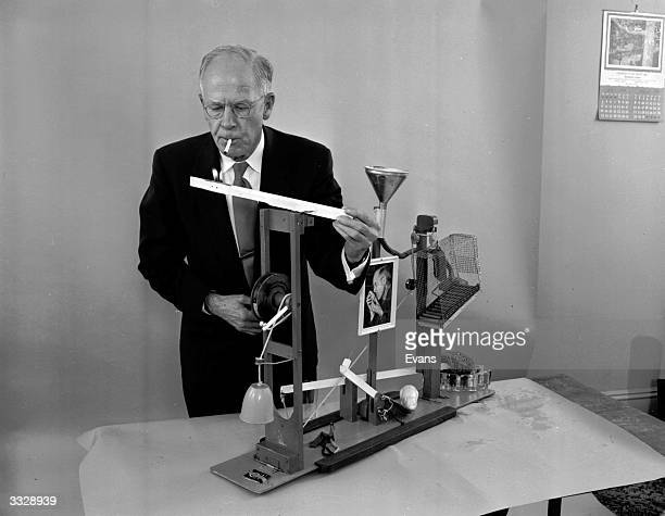 American amateur inventor Russell E Oakes demonstrates his complex cigarette lighter which is catalysed by a glass of water