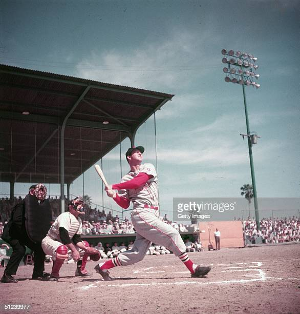 American baseball player Stan Musial watches the ball as he follows through after a hit during a game circa 1955 Musial wears the uniform of the St...