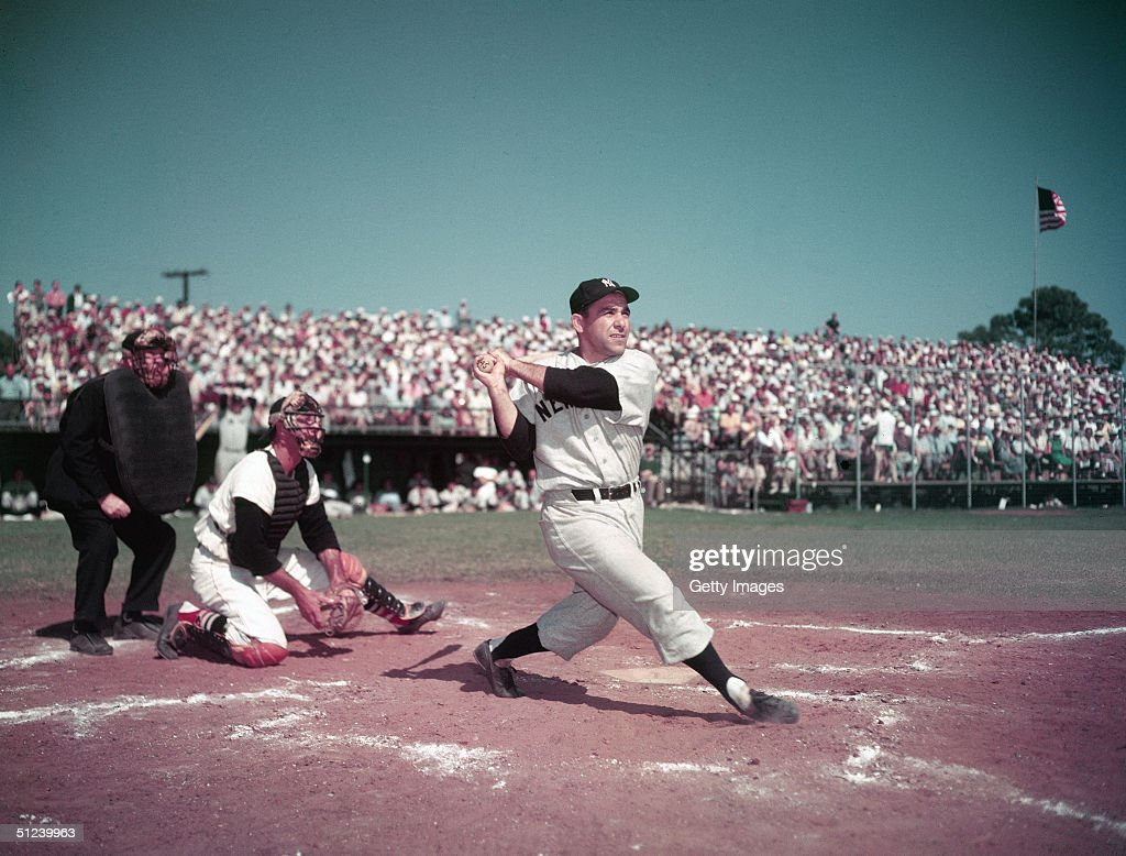 Circa 1955, American baseball player Yogi Berra, catcher for for the New York Yankees, swinging the bat during a game, 1950s.
