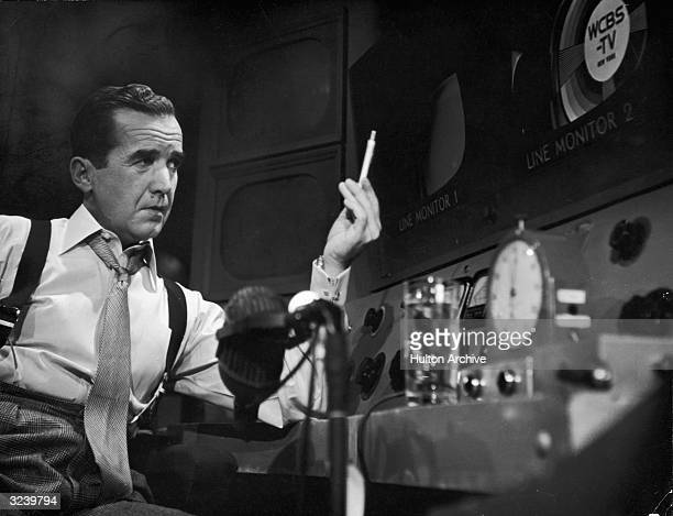 American broadcast journalist Edward R Murrow sits behind a console in a CBS television control room holding a pen in the air 1950s There is a...