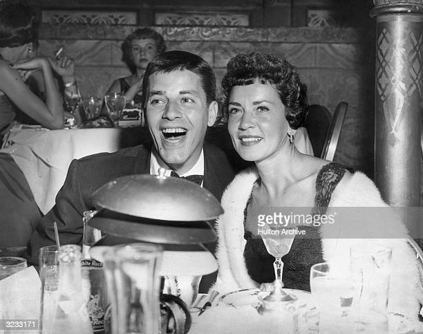 American comedian and actor Jerry Lewis laughing as he sits next to his first wife Patti in a restaurant