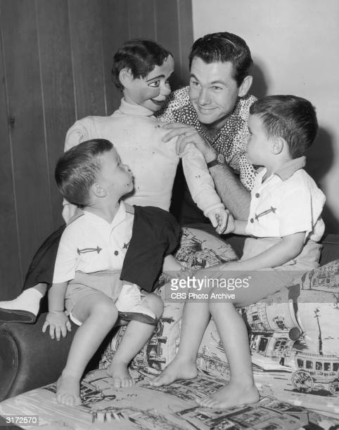 American comedian and television show host Johnny Carson plays with a ventriloquist's dummy as his sons Ricky and Kit look on