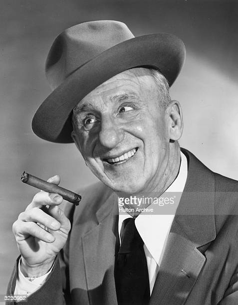 American comedian Jimmy Durante smiling and holding a cigar. He wears a hat at an angle.