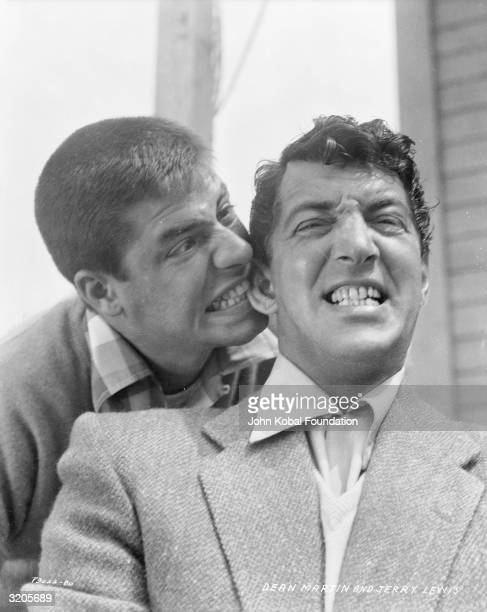American comic Jerry Lewis sinks his teeth into the ear of costar Dean Martin