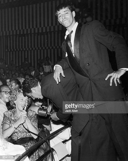 American comic team Dean Martin and Jerry Lewis standing on stage during a nightclub act as they give the microphone to singer and actor Vivian...