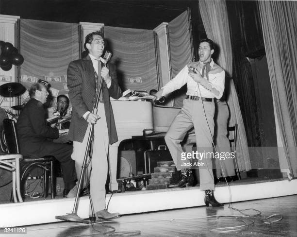 American comic team Jerry Lewis and Dean Martin sing into microphones onstage while performing at a SHARE Boomtown party for charity Behind them sits...