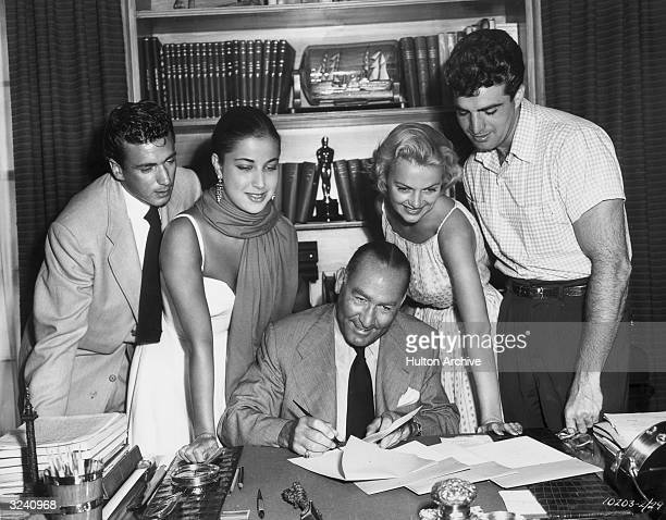 American film producer Hal Wallis signing the contracts of four young actors at the Paramount Studios lot, Hollywood, California. L-R: Richard...