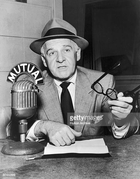 American gossip columnist and broadcast journalist Walter Winchell speaks into a microphone during a radio broadcast