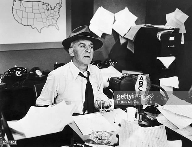 American journalist Walter Winchell sits at a desk strewn with loose sheets of paper during an ABC radio broadcast
