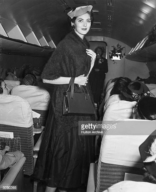 American model Carmen Dell'Orefice wears a hat and a mohair wrap and carries a purse while walking in the aisle of an airplane during a fashion show