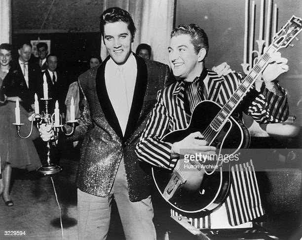 American musicians Elvis Presley and Liberace exchange personal trademarks while standing together Presley holds a candelabra while Liberace plays...