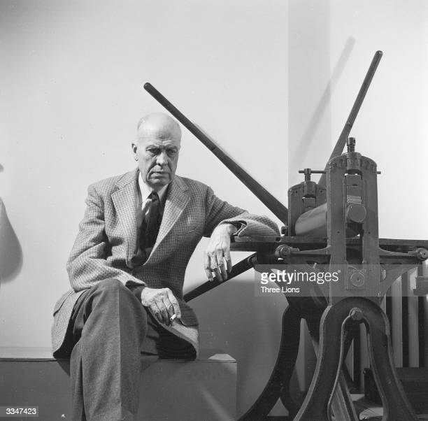 American realist painter Edward Hopper sitting by a manual printing press in his Greenwich Village studio