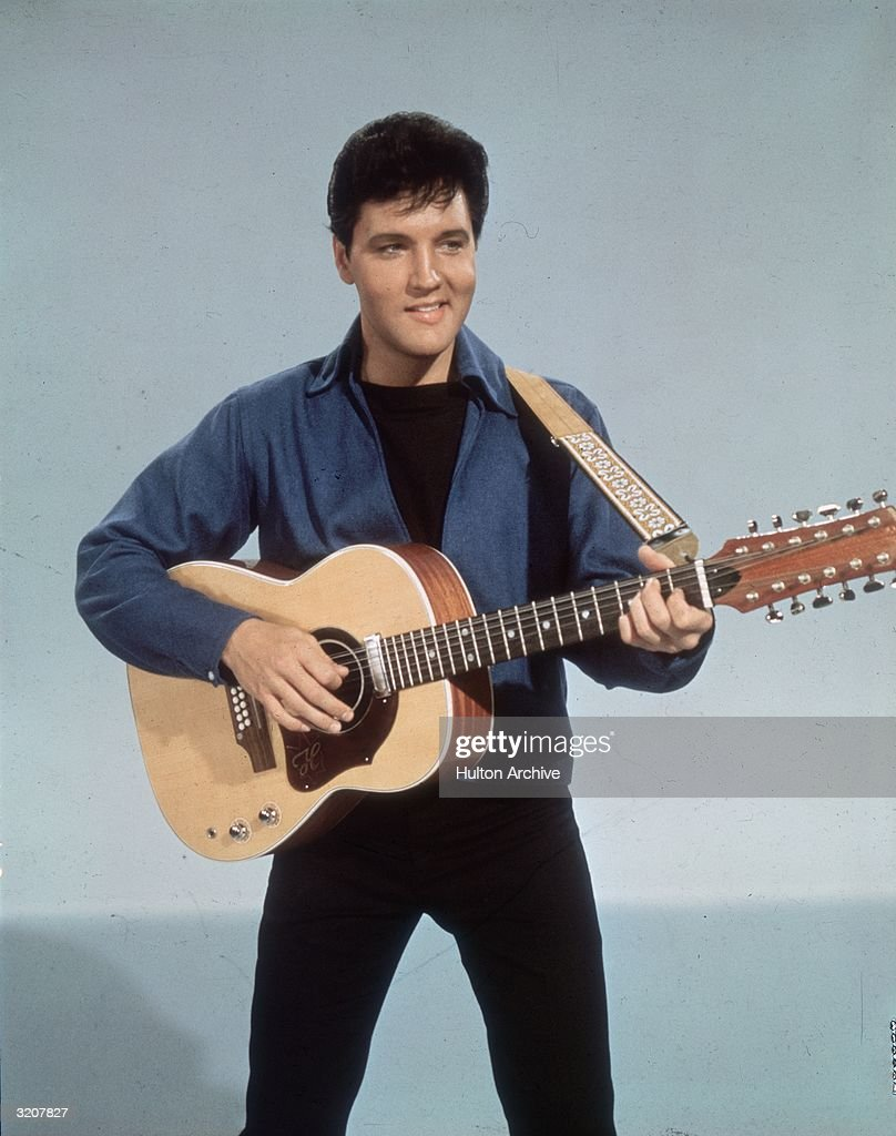 American rock 'n roll singer Elvis Presley (1935 - 1977) with a twelve string guitar.