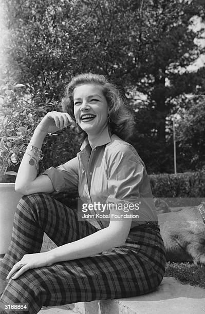 American screen star Lauren Bacall wearing checked trousers and a charm bracelet