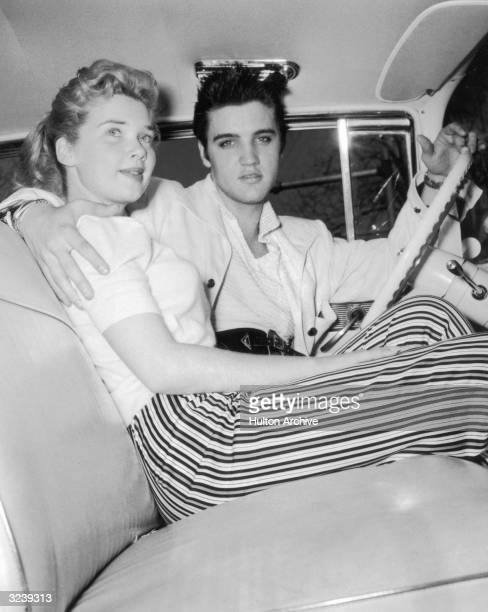 American singer and actor Elvis Presley sits in the driver's seat of a car with his arm around an unidentified young woman