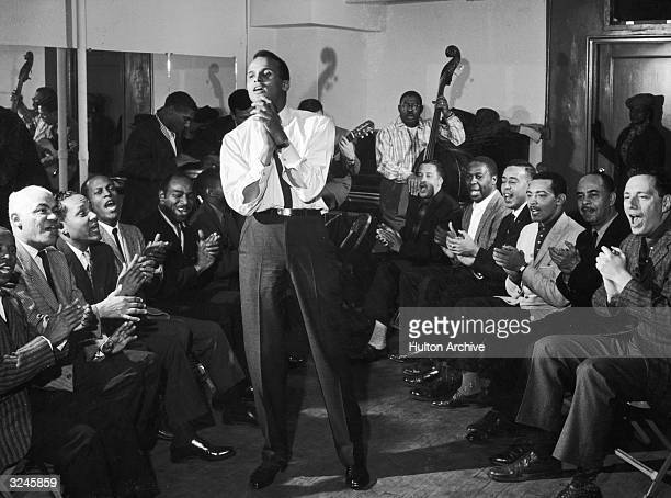 American singer and musician Harry Belafonte Jr. Sings and claps his hands along with a group of men sitting around him. A band plays in the back of...