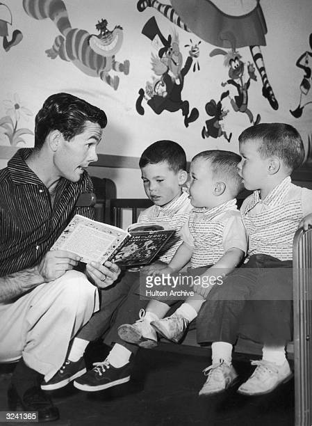 American television host Johnny Carson kneels while he reads a children's book to his sons Kit Cory and Ricky in their nursery There are cartoon...