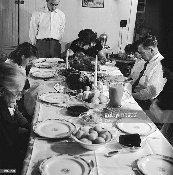 An American family say grace before starting on the Thanksgiving turkey