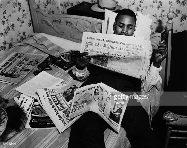 An American man reads of events concerning civil rights in the newspapers