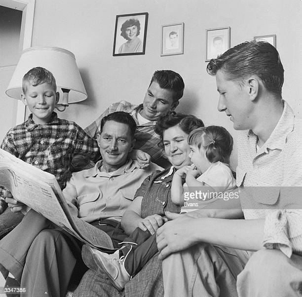 An American Methodist Church sexton sitting on a sofa with his wife and children at home in California They are all reading a newspaper