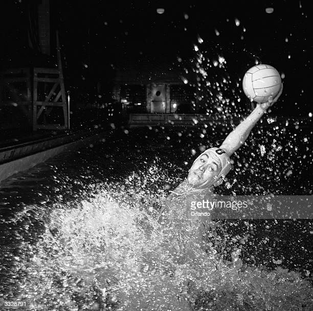An American water polo player rises from the deep to make a pass to a team mate in the New York Athletic Club water polo team