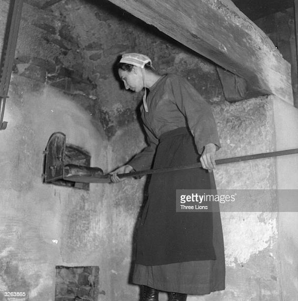 An Amish woman removing a freshly baked loaf from an outdoor naturally powered oven