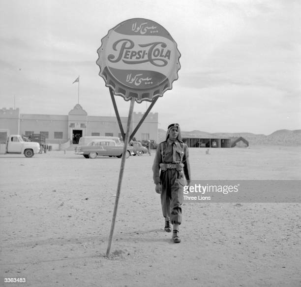 An incongruous sign in the Kuwaiti desert advertising PepsiCola American soft drinks are popular in Kuwait where the Muslim population is forbidden...